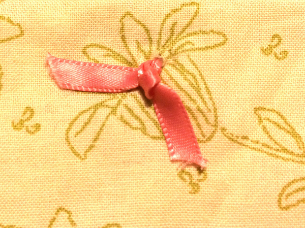 Quilting knot tied with pink ribbon