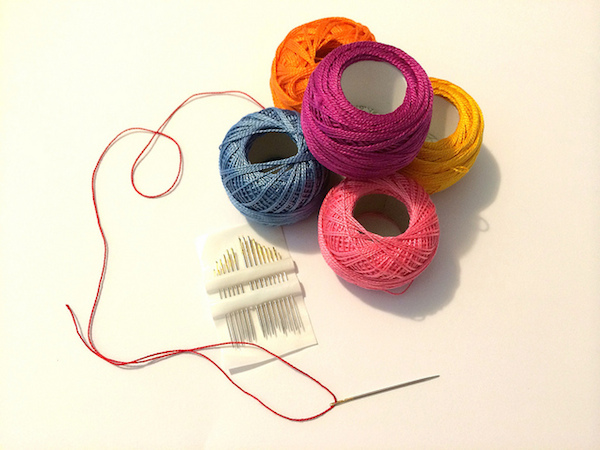 Embroidery needles next to balls of perle thread