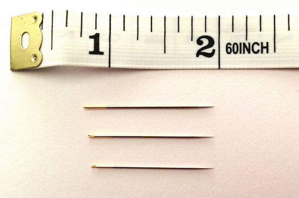 3 quilting needles next to a tape measure
