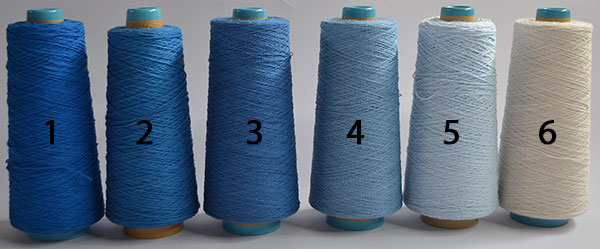 Six cones of yarn in shades of blue
