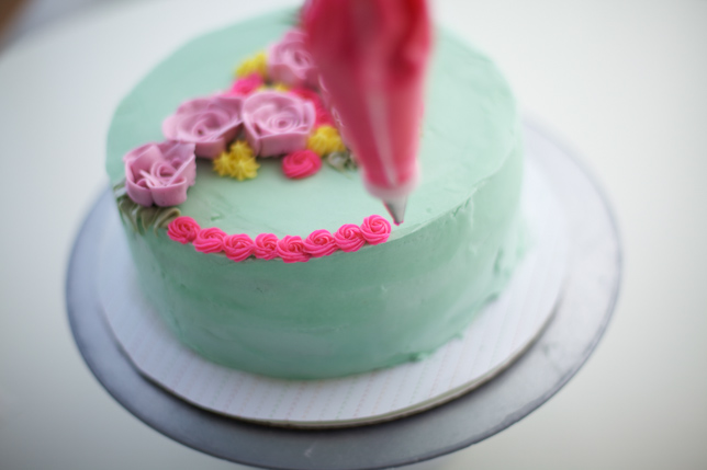 adding foliage to the bouquet cake with a piping bag
