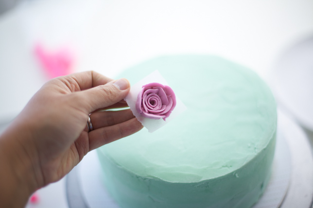 placing buttercream rose on layer cake