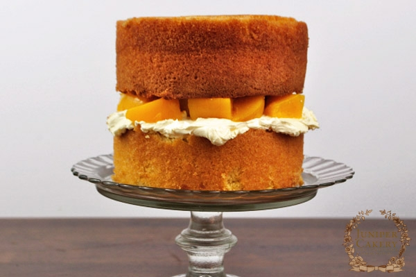 Overfilled peach and white chocolate cake by Juniper Cakery
