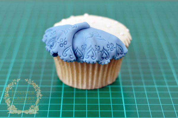cupcake decorated with blue lace printed fondant
