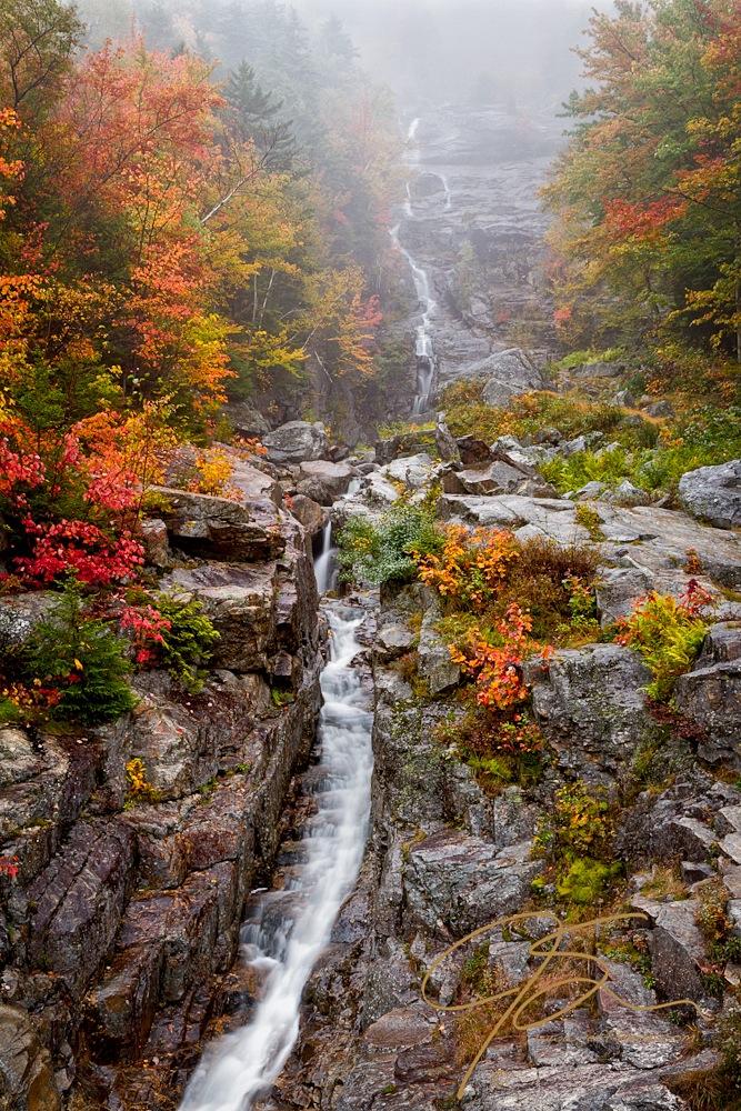 Silvery cascading waterfall through an autumn forest