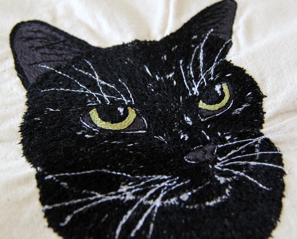 Free-hand machine embroidery of black cat on calico