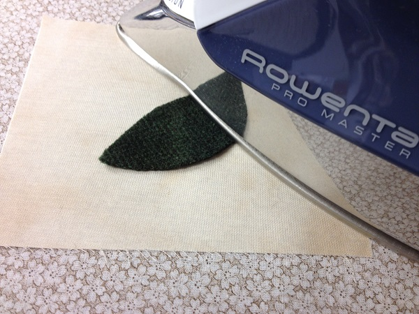pressing wool shape to background fabric with iron