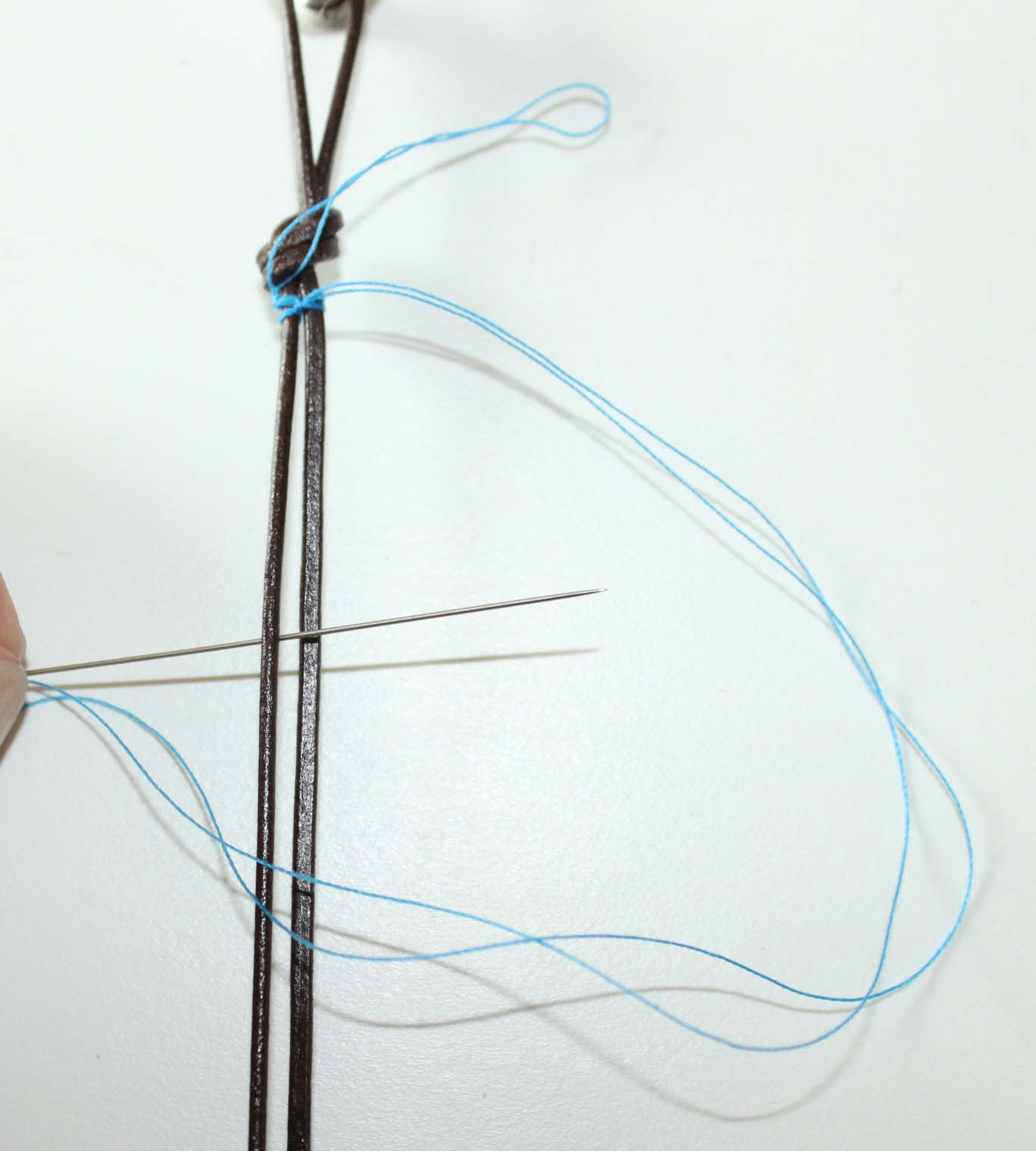 Adding thread to leather by looping over, under and between leather cords