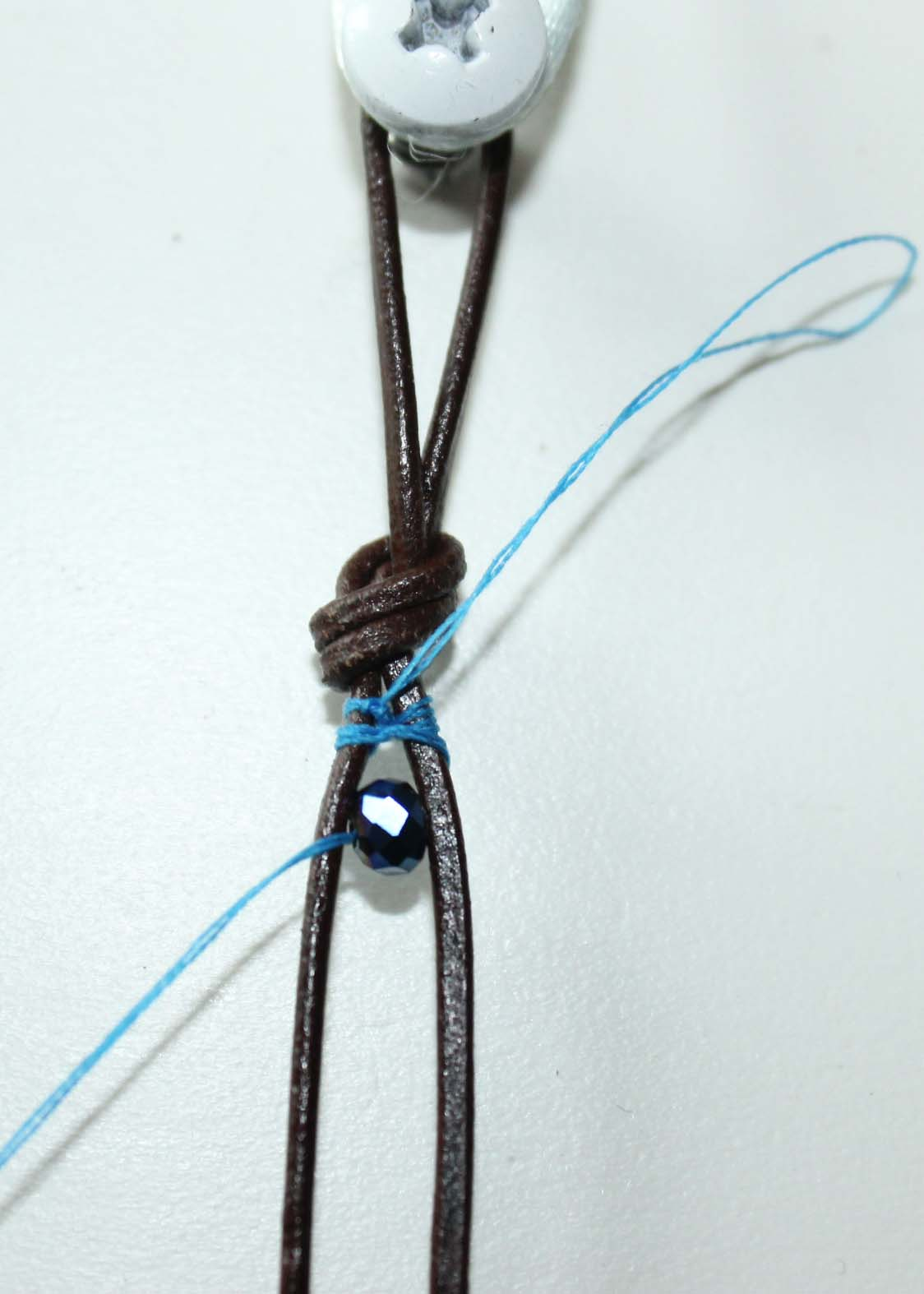 Add first bead to the leather cords