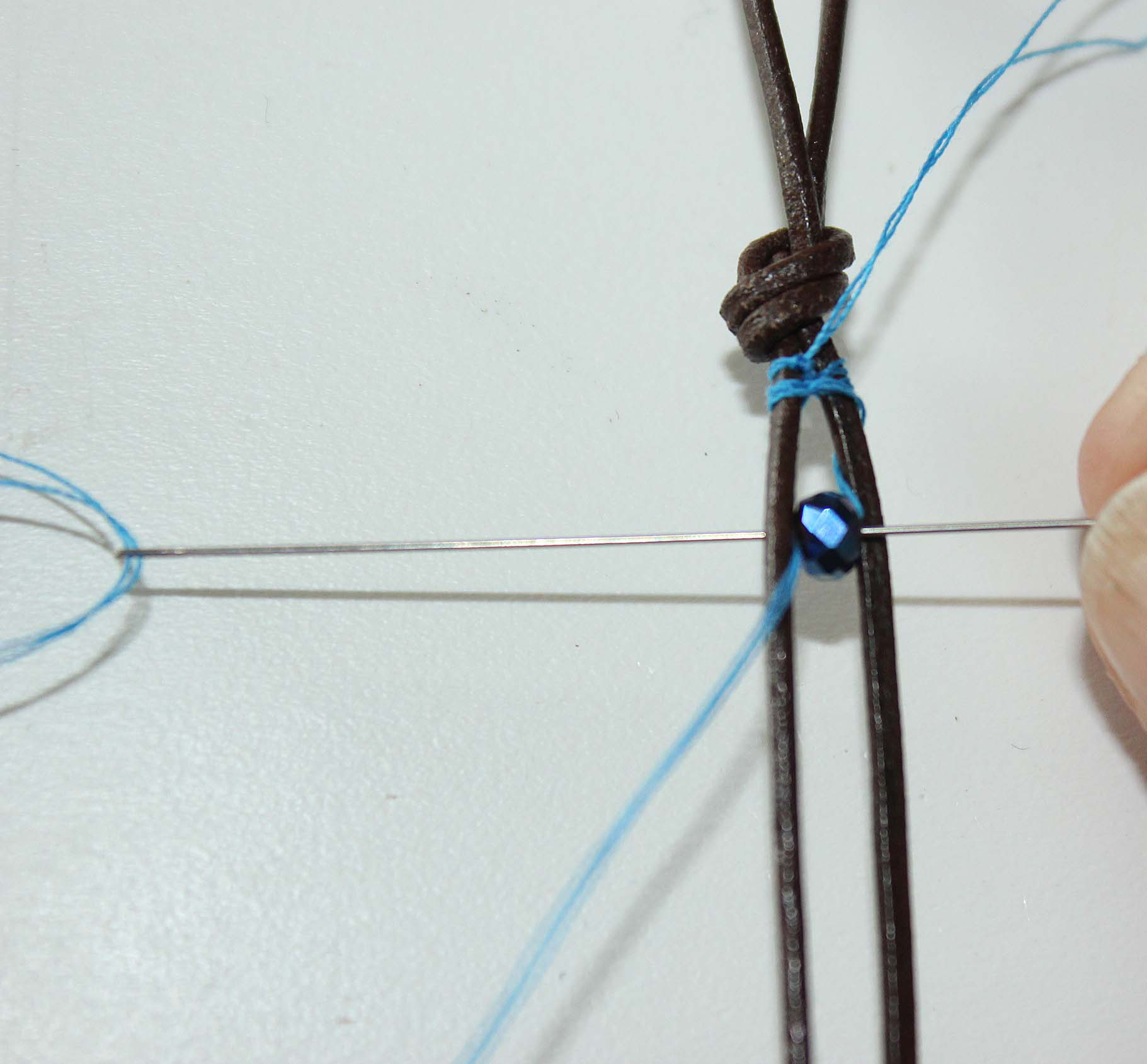 Adding first bead. Thread over top of leather, under leather cord and back through first bead again.