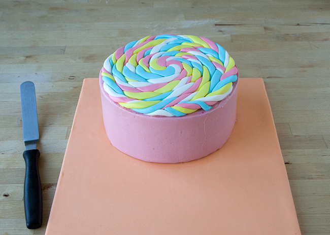 Place fondant lollipop disk on top of layer cake