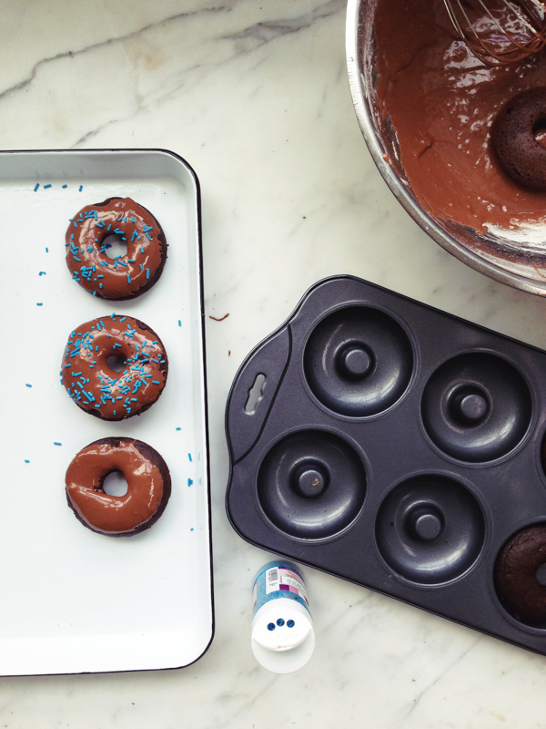 Glazing the Baked Chocolate Doughnuts