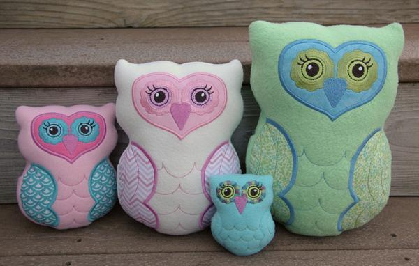 4 owl plushies against a wooden background