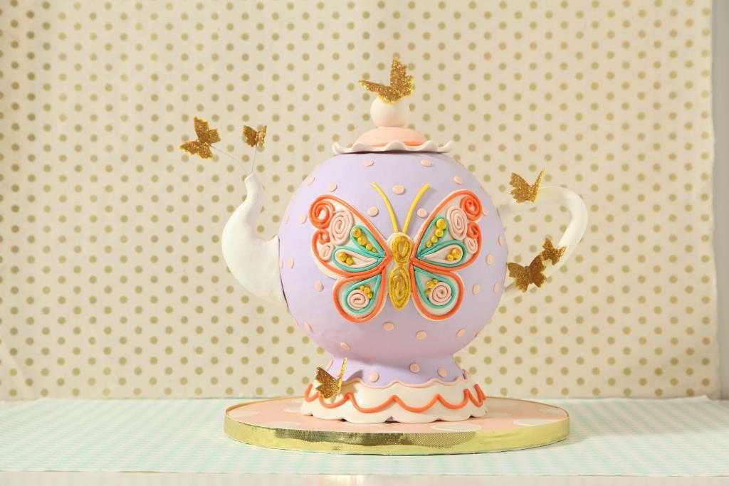 Whimsical teapot cake with floating butterflies