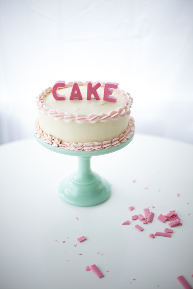 buttercream cake with pink lettering spelling CAKE