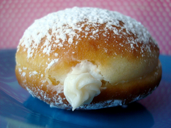 Finishing a cream filled doughnut with confectioner's sugar