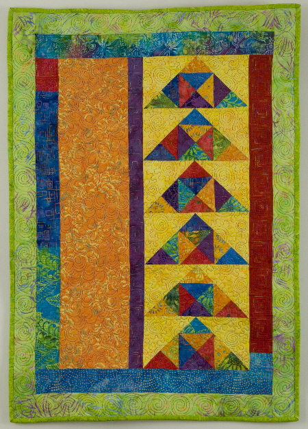 Colorful wall quilt with modern flying geese