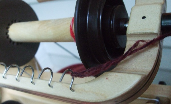yarn tied to a hook of a spinning wheel flyer