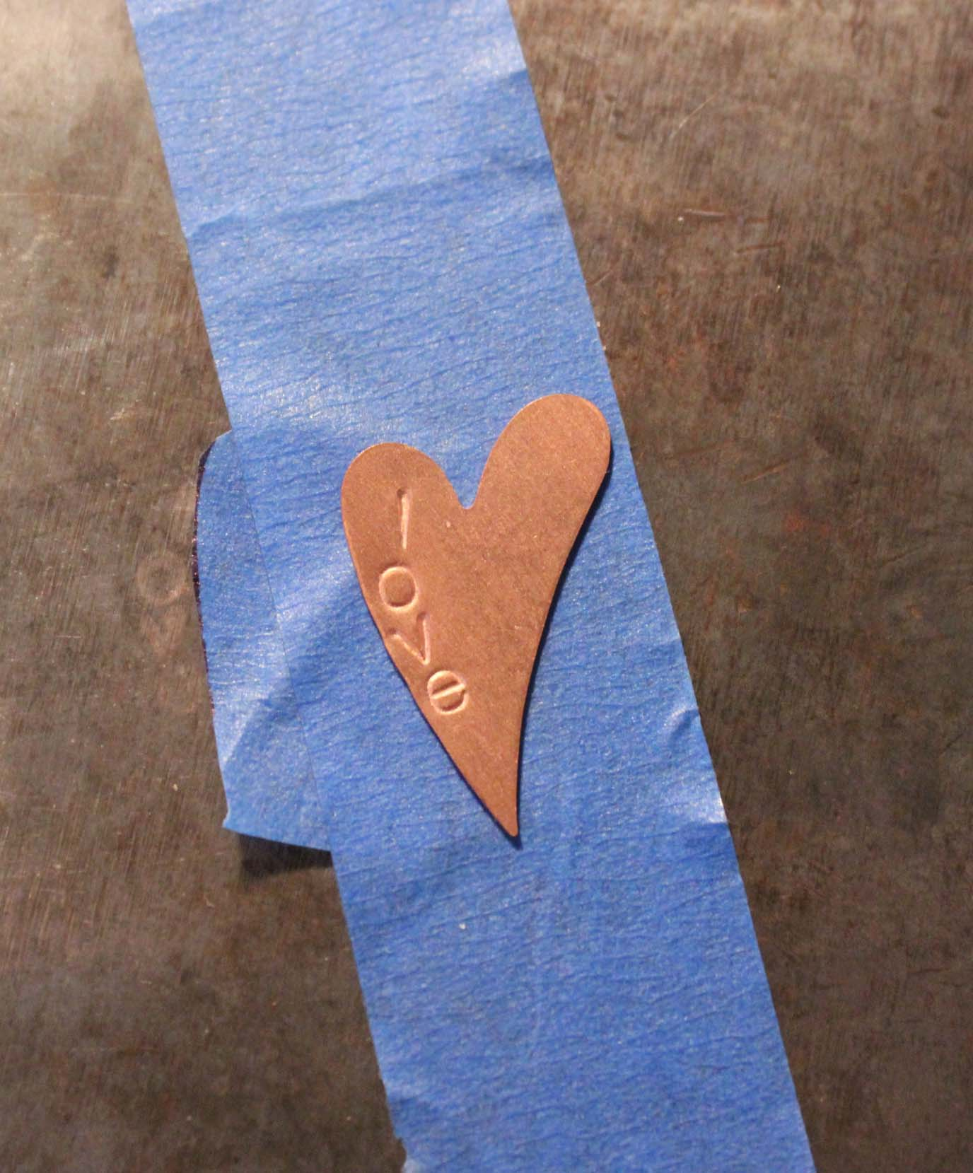 Heart shaped blank has been stamped with the letters l-o-v-e
