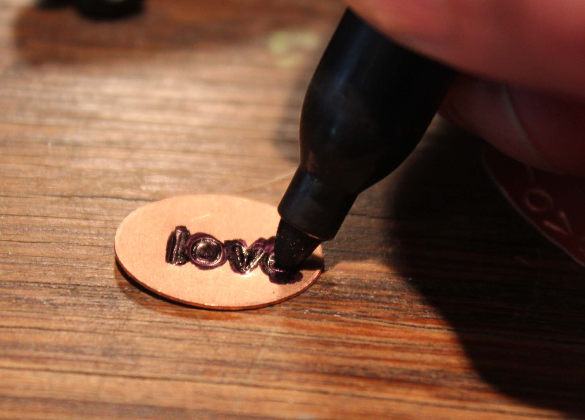 A permanent marker being used to darken the impressed letters