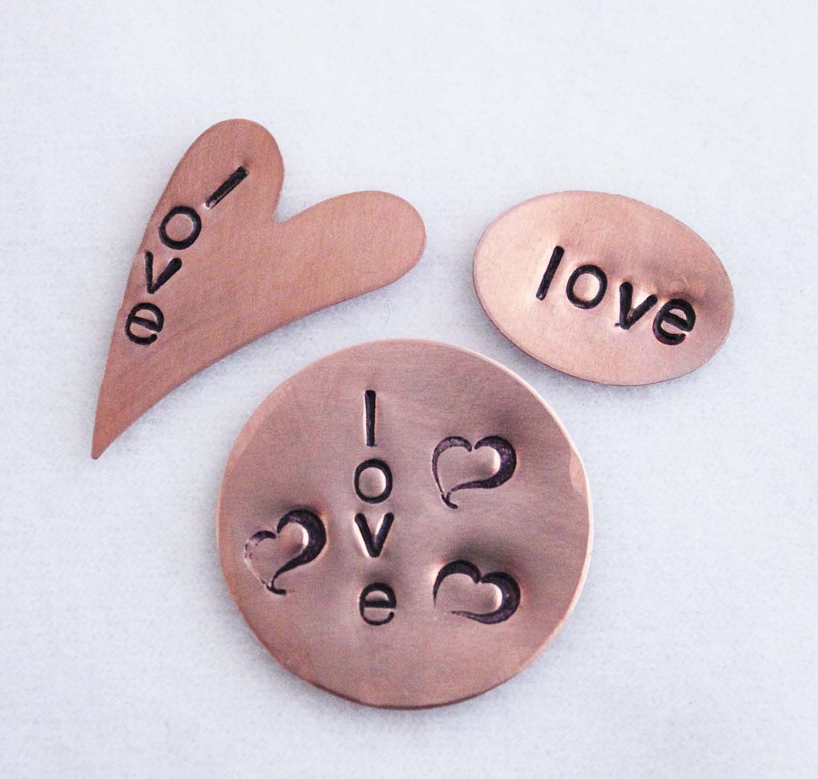Three different shaped blanks hand stamped with the word love