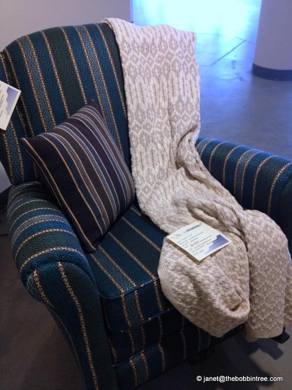 chair covered with handwoven fabric and a blanket and pillow