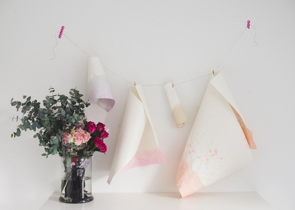 Dyed Paper Hanging Next to a Bouquet of Flowers