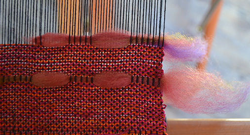 placement of wool sliver at the edge of a weaving in progress