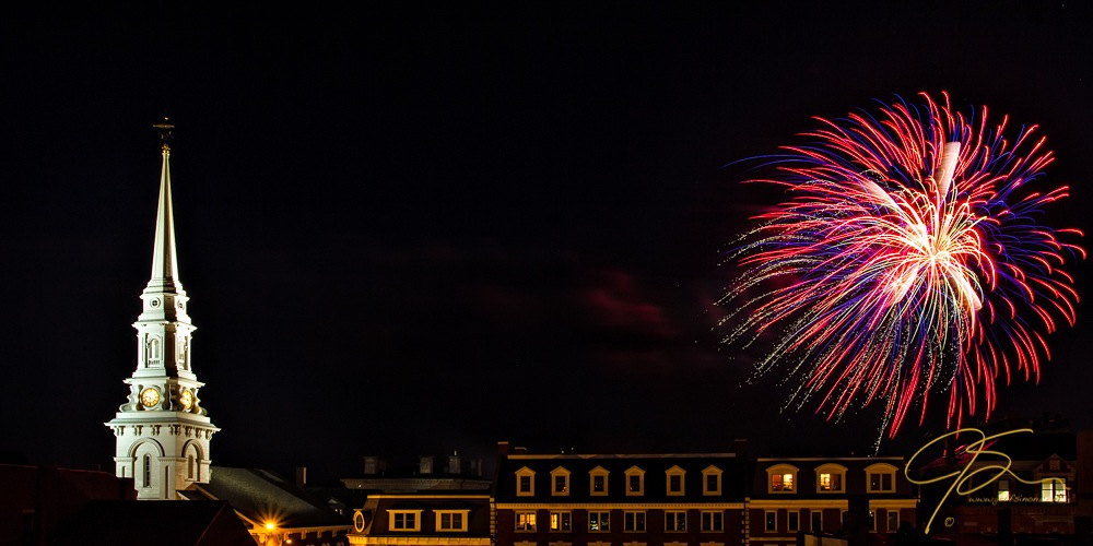 The North Church steeple and a burst of fireworks rise above the rooftops of Portsmouth, NH
