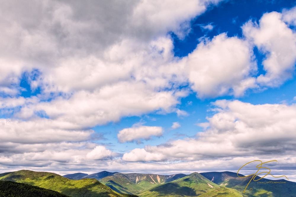 A sky full of billowy white clouds drifts over the New Hampshire mountains.