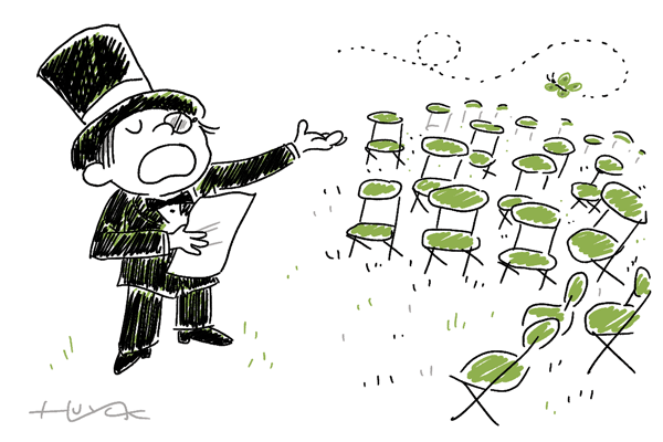 A boy in a tux reads poetry to a bunch of empty chairs.