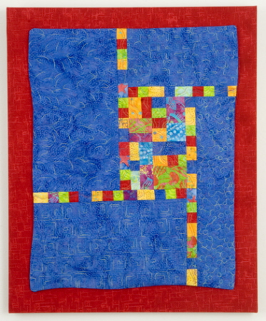 Blue wall quilt with primary blocks