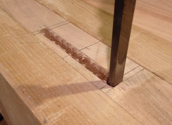 Using a mortise chisel to clean out a mortise