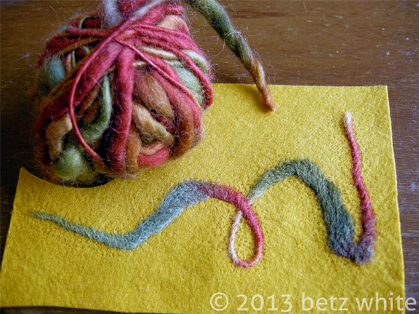 Felted yellow fabric with red and blue swirl