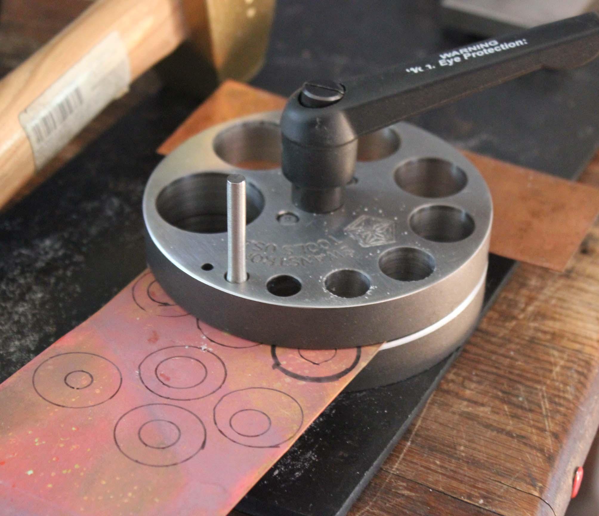 Insert copper sheet into disc cutter. Punch inner disc first.