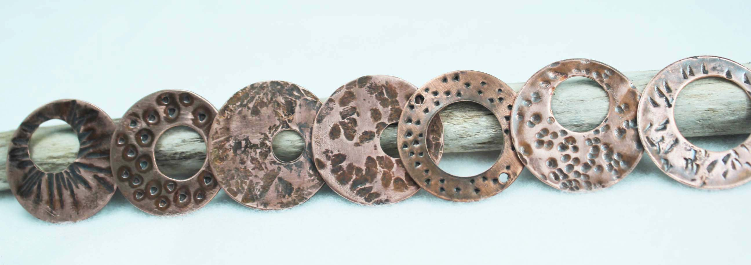 Seven copper discs sporting a variety of added textures