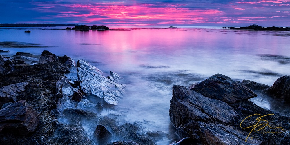 dark foreground rocks and the bright pink sky along the ocean