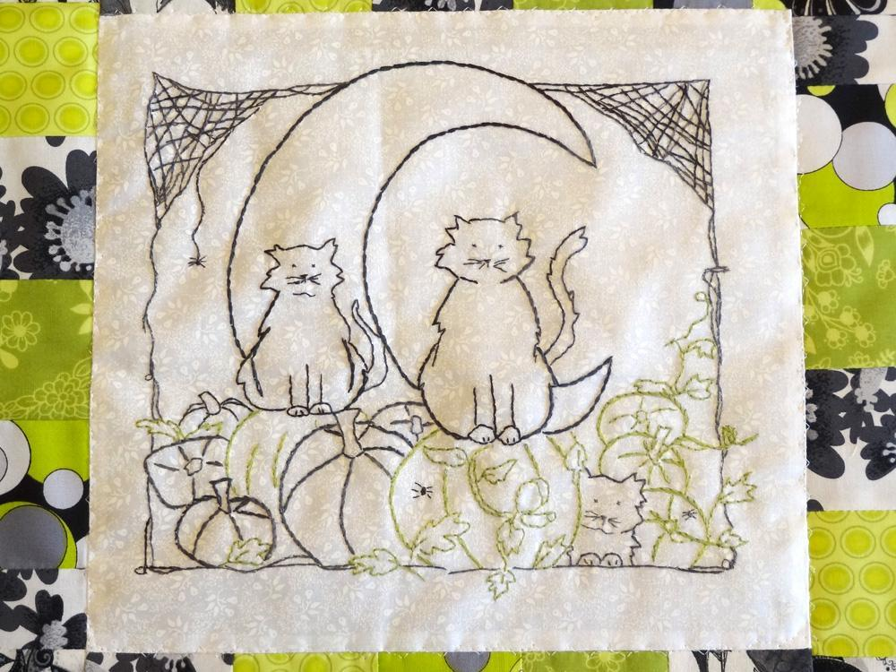 hand embroidery pattern of two black cats sitting on pumpkins surrounded by cobwebs