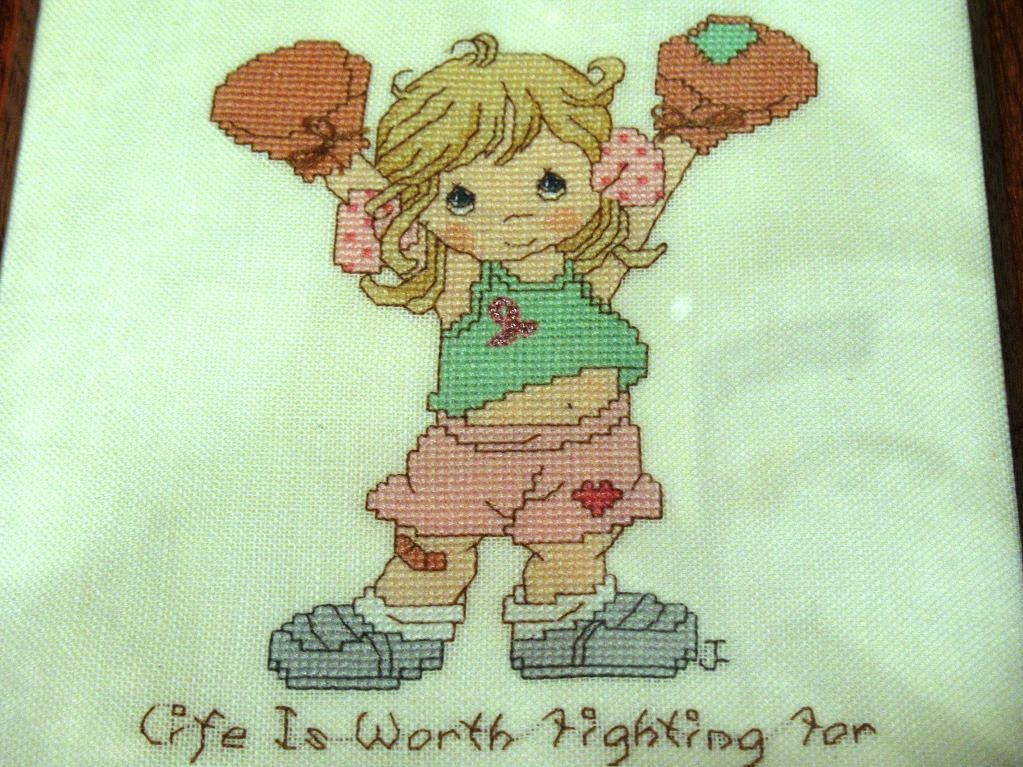 cross stitch pattern of girl in boxing gloves wearing pink ribbon