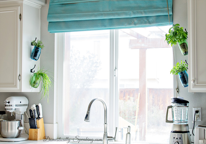 Kitchen Window Adorned With Hanging Herb Jars