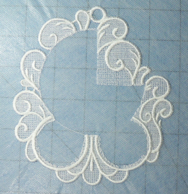 Freestanding lace on water soluble adhesive mesh stabilizer