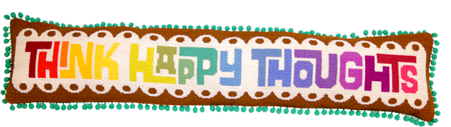 long rectangular cushion with the phrase think happy thoughts in rainbow needlepoint