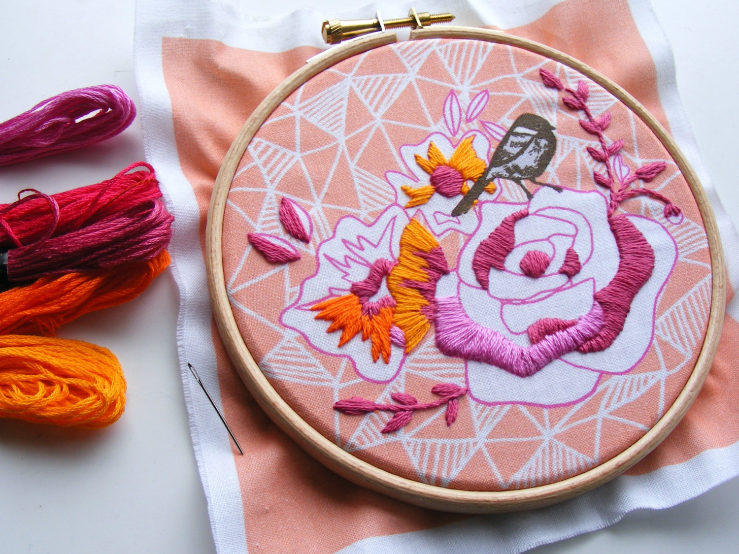hand embroidered pink and orange rose on geometric fabric