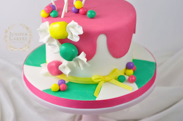 Adding fondant candy decorations to a candy themed birthday cake