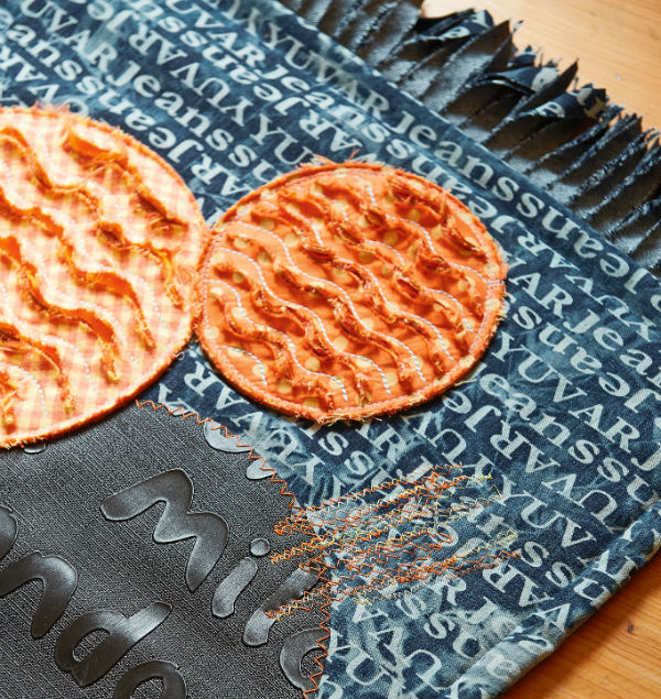 Denim rug with applique and embroidery.