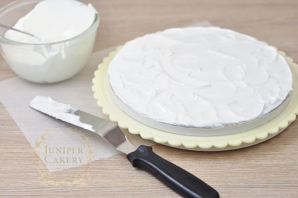 Add royal icing to a cake board for a rustic snow effect