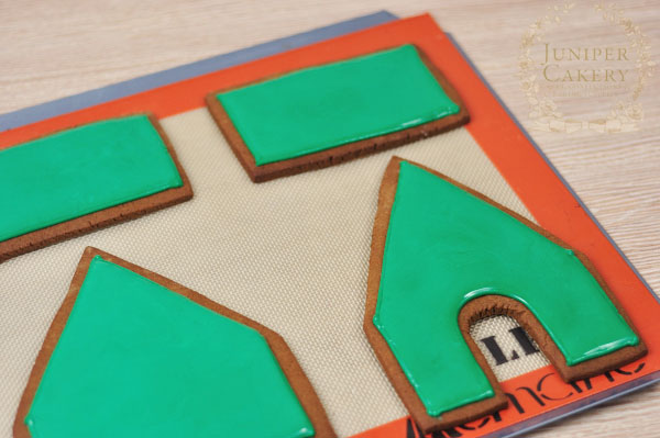 Flood icing a gingerbread house with royal icing by Juniper Cakery