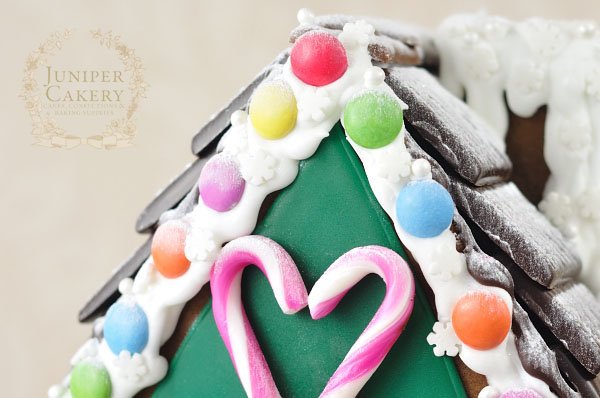 Decorating a festive gingerbread house with cookies, candies and sprinkles