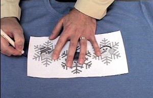 Marking embroidery crosshair location on a shirt.