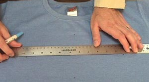 Marking embroidery design center on shirt.